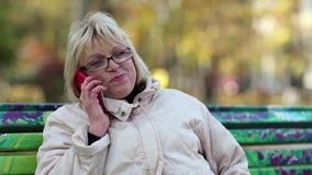 Η γυναίκα κάθεται στον πάγκο και μιλά στο κόκκινο smartphone φιλμ μικρού μήκους