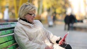 Η γυναίκα κάθεται στον πάγκο στο πάρκο πόλεων και επικοινωνεί μέσω του κόκκινου smartphone φιλμ μικρού μήκους