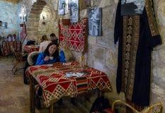 Η γυναίκα κάθεται στον πίνακα και πίνει τον καφέ σε ένα εστιατόριο ακρών του δρόμου κοντά στην πόλη Wadi μούσα στην Ιορδανία στοκ φωτογραφίες