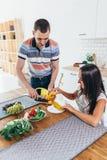 Η γυναίκα κάθεται στον πίνακα κουζινών τρώει τη συζήτηση καλαμποκιού με το τέμνον καλαμπόκι ανδρών στοκ εικόνα