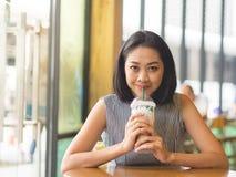 Η γυναίκα κάθεται στον παγωμένο καφέ καφέδων καφέ wirh στον πίνακα στοκ εικόνες