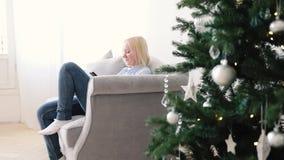 Η γυναίκα κάθεται στο χριστουγεννιάτικο δέντρο Smartphone χρήσεων καναπέδων απόθεμα βίντεο