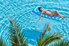 Η γυναίκα κάνει ηλιοθεραπεία στο διογκώσιμο στρώμα στη λίμνη στοκ φωτογραφία με δικαίωμα ελεύθερης χρήσης