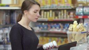 Η γυναίκα κάνει τα αγαθά στη βάση δεδομένων στο κατάστημα κατοικίδιων ζώων, κατάλογος του καταστήματος απόθεμα βίντεο