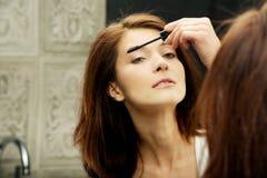 Η γυναίκα κάνει την ελαφριά ημέρα makeup στο λουτρό στοκ εικόνα με δικαίωμα ελεύθερης χρήσης