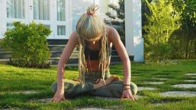 Η γυναίκα κάνει την κοιλιά την κενή συνεδρίαση άσκησης στο χορτοτάπητα στο κατώφλι του σπιτιού φιλμ μικρού μήκους