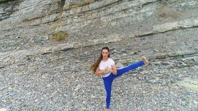Η γυναίκα κάνει τη γιόγκα και τις σωματικές ασκήσεις για τα πόδια στο υπόβαθρο βράχου Εναέρια όμορφη άποψη μήκους σε πόδηα απόθεμα βίντεο
