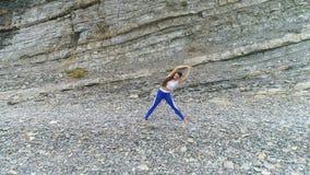 Η γυναίκα κάνει τη γιόγκα και τις σωματικές ασκήσεις στο υπόβαθρο βράχου και θάλασσας Εναέρια όμορφη άποψη μήκους σε πόδηα απόθεμα βίντεο
