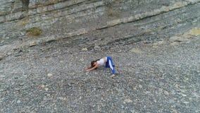 Η γυναίκα κάνει τη γιόγκα και bodyflex οι ασκήσεις στο υπόβαθρο βράχου και θάλασσας Εναέρια όμορφη πλάγια όψη μήκους σε πόδηα απόθεμα βίντεο
