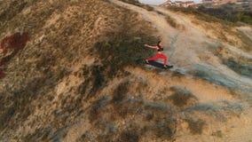 Η γυναίκα κάνει τη γιόγκα που το υψηλό μεσημεριανό γεύμα θέτει στην κορυφή του βουνού στο ηλιοβασίλεμα Εναέριο όμορφο μήκος σε πό απόθεμα βίντεο