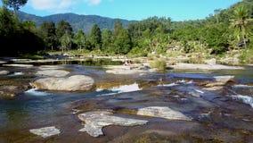 Η γυναίκα κάνει τη γυμναστική στο βράχο μεταξύ του ρέοντας ποταμού φιλμ μικρού μήκους