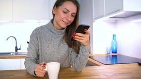 Η γυναίκα κάνει τη σε απευθείας σύνδεση πληρωμή στο σπίτι με μια πιστωτική κάρτα και ένα smartphone απόθεμα βίντεο