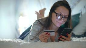 Η γυναίκα κάνει τη σε απευθείας σύνδεση πληρωμή στο σπίτι με μια πιστωτική κάρτα και ένα smartphone φιλμ μικρού μήκους