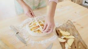 Η γυναίκα κάνει τη φρέσκια πίτα μήλων στην κουζίνα της φιλμ μικρού μήκους