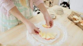 Η γυναίκα κάνει τη φρέσκια πίτα μήλων στην κουζίνα της απόθεμα βίντεο
