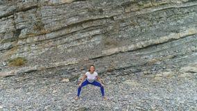 Η γυναίκα κάνει τις στάσεις οκλαδόν που το bodyflex κατά τη διάρκεια της αναπνοής ασκεί στο υπόβαθρο βράχου Εναέρια όμορφη άποψη  φιλμ μικρού μήκους