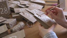 Η γυναίκα κάνει το ημερολόγιο εμφάνισης Χριστουγέννων για τα παιδιά Γράφει έναν αριθμό στην τσάντα από τη βούρτσα και το άσπρο χρ απόθεμα βίντεο
