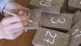 Η γυναίκα κάνει το ημερολόγιο εμφάνισης Χριστουγέννων για τα παιδιά Γράφει έναν αριθμό στην τσάντα από τη βούρτσα και το άσπρο χρ φιλμ μικρού μήκους
