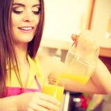 Η γυναίκα κάνει το χυμό από πορτοκάλι στο χύνοντας ποτό μηχανών juicer στο ποτήρι Στοκ Φωτογραφία