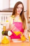 Η γυναίκα κάνει το χυμό από πορτοκάλι στο χύνοντας ποτό μηχανών juicer στο ποτήρι Στοκ φωτογραφίες με δικαίωμα ελεύθερης χρήσης