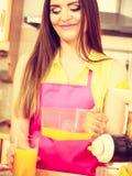 Η γυναίκα κάνει το χυμό από πορτοκάλι στο χύνοντας ποτό μηχανών juicer στο ποτήρι Στοκ Φωτογραφίες