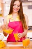 Η γυναίκα κάνει το χυμό από πορτοκάλι στο χύνοντας ποτό μηχανών juicer στο ποτήρι Στοκ εικόνες με δικαίωμα ελεύθερης χρήσης