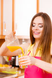 Η γυναίκα κάνει το χυμό από πορτοκάλι στο χύνοντας ποτό μηχανών juicer στο ποτήρι στοκ φωτογραφία με δικαίωμα ελεύθερης χρήσης