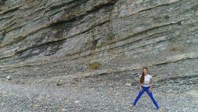 Η γυναίκα κάνει plie τις στάσεις οκλαδόν που το bodyflex κατά τη διάρκεια της αναπνοής ασκεί στο υπόβαθρο βράχου Εναέρια όμορφη ά φιλμ μικρού μήκους