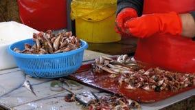 Η γυναίκα καθαρίζει και κόβει τα φρέσκα ψάρια στην αγορά ψαριών απόθεμα βίντεο