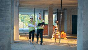 Η γυναίκα και ο άνδρας εργάζονται με ένα σχεδιάγραμμα οικοδόμησης περπατώντας, κλείνουν επάνω απόθεμα βίντεο