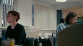 Η γυναίκα και ο άνδρας εργάζονται στο γραφείο στους υπολογιστές απόθεμα βίντεο