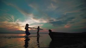 o Η γυναίκα και ο άνδρας κρατούν τα χέρια και τρέχουν χαρωπά κατά μήκος της λίμνης στο ηλιοβασίλεμα Σκιαγραφίες μικρά παιδιά απόθεμα βίντεο