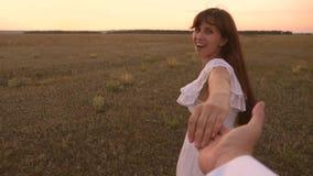 Η γυναίκα και ο άνδρας με ακολουθούν Τα τρεξίματα κοριτσιών πέρα από τον τομέα που κρατά το χέρι του αγαπημένου ατόμου της και γε απόθεμα βίντεο
