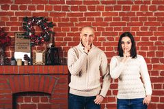Η γυναίκα και ο άνδρας σε ένα υπόβαθρο τουβλότοιχος παρουσιάζουν shhh στοκ εικόνα με δικαίωμα ελεύθερης χρήσης