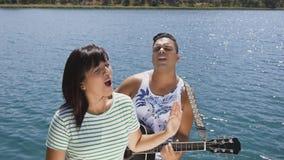 Η γυναίκα και ο άνδρας τραγουδούν ένα τραγούδι με μια κιθάρα απόθεμα βίντεο