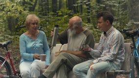 Η γυναίκα και ο άνδρας Eldery με το νέο τύπο πίνουν το τσάι στον πάγκο στο πάρκο φιλμ μικρού μήκους