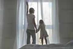 Η γυναίκα και το μικρό κορίτσι, ξυπνήστε και ανοίγουν τις κουρτίνες το πρωί, πίσω άποψη Στοκ εικόνες με δικαίωμα ελεύθερης χρήσης