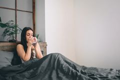 Η γυναίκα καλημέρας ξύπνησε στο κρεβάτι πίνοντας γυναίκα καφέ σπορείων Στοκ Εικόνες