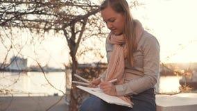 Η γυναίκα καλλιτεχνών σύρει τη συνεδρίαση εικόνων σε ένα πάρκο στο ηλιοβασίλεμα απόθεμα βίντεο