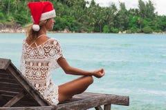 Η γυναίκα καπέλων Χριστουγέννων σε μια γιόγκα θέτει στην παραλία thel Στοκ Φωτογραφίες