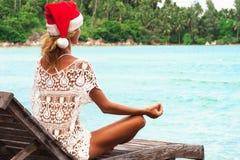 Η γυναίκα καπέλων Χριστουγέννων σε μια γιόγκα θέτει στην παραλία thel Στοκ Εικόνα