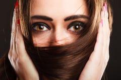 Η γυναίκα κινηματογραφήσεων σε πρώτο πλάνο καλύπτει το πρόσωπο από τη μακριά καφετιά τρίχα στοκ φωτογραφία