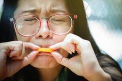 Η γυναίκα κινηματογραφήσεων σε πρώτο πλάνο πορτρέτου αισθάνεται ξινή με τα πορτοκαλιά φρούτα Στοκ Εικόνα