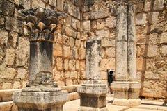 Η γυναίκα κλίνει στην πόρτα του τουβλότοιχος βασαλτών στις αρχαίες καταστροφές Capernaum Στοκ Φωτογραφία