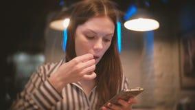 Η γυναίκα κοιτάζει βιαστικά Διαδίκτυο στο κινητό τηλέφωνό της και τρώει τις τηγανιτές πατάτες απόθεμα βίντεο