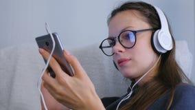 Η γυναίκα κοιτάζει βιαστικά και κοιτάζει στα κοινωνικά μέσα στο smartphone στα γυαλιά και τα ακουστικά απόθεμα βίντεο