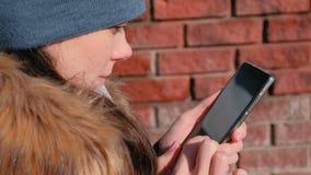Η γυναίκα κοιτάζει βιαστικά τις σελίδες Διαδικτύου στο κινητό τηλέφωνο στο χειμερινό πάρκο Πρόσωπο κινηματογραφήσεων σε πρώτο πλά απόθεμα βίντεο