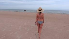 Η γυναίκα κοιτάζει γύρω από και περίπατος στη θάλασσα φιλμ μικρού μήκους