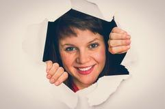 Η γυναίκα κοιτάζει μέσω μιας τρύπας στο σχισμένο έγγραφο στοκ εικόνα με δικαίωμα ελεύθερης χρήσης