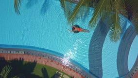 Η γυναίκα κολυμπά στο δαχτυλίδι στη λίμνη κάτω από τους φοίνικες απόθεμα βίντεο